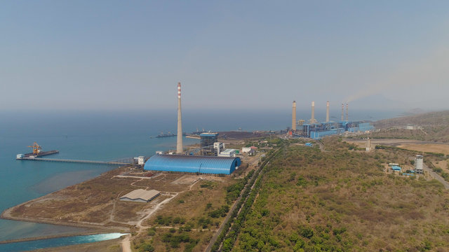 power station by sea with smoking pipes, paiton java, indonesia. aerial view power plant in asia.
