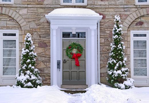 front door with colorful wreath in winter scene
