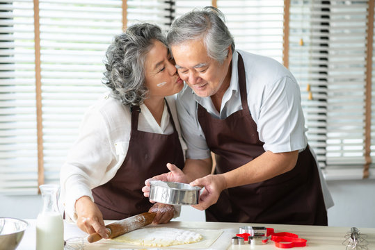 Asian Grandmother kissing Grandfather while their baking cookies.