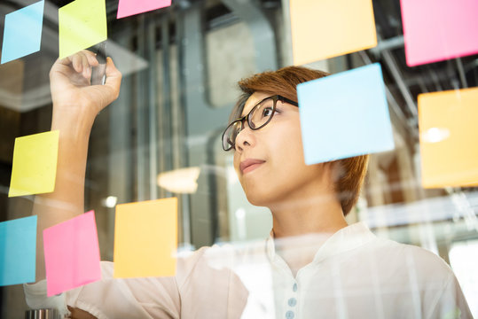 Young woman designer writing new ideas at sticky notes.