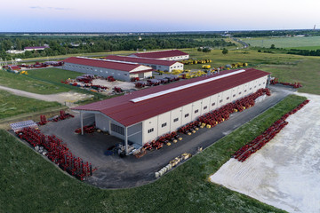 The territory of an industrial plant. Large hangars with a red roof. Aerial view, evening shooting