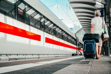 Frau auf dem Bahnsteig geht mit Gepäck den Zug entlang