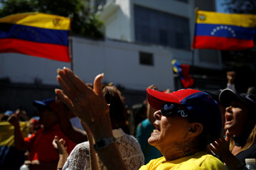 Opposition supporters waving Venezuelan flags take part in a gathering with members of Venezuela's National Assembly in La Guaira