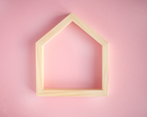 Wooden frame in the shape of a house on pink background