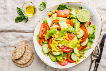 Healthy vegetable salad of fresh tomato, cucumber, lettuce and corn on plate, top view. Diet menu.