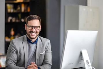 Portrait of handsome businessman smiling at camera while sitting in front of computer at the office desk
