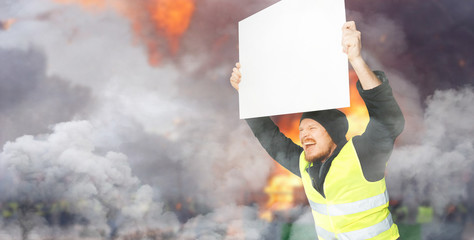 Protests yellow vests. A young man is holding a poster. Concept of revolution and protest, struggle...