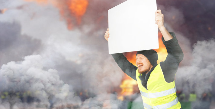 Protests yellow vests. A young man is holding a poster. Concept of revolution and protest, struggle for equal rights, electoral movement