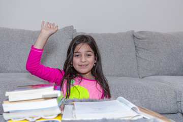 A young girl, front of a pile of books, is raising her hand to ask or answer a question