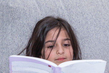 Close up shot of a young girl reading a book