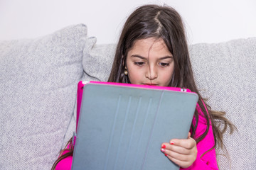 Young girl is playing with her tablet in a couch