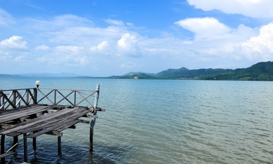 A broke pier into the tropical sea overlooking the distant mountains