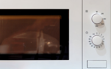 Turned on classic microwave oven. Closeup.