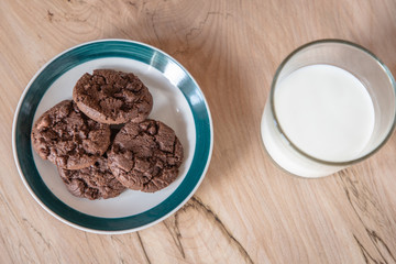A cup of milk and plate of cookies of a brown desk