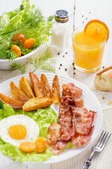 English breakfast-plate with fried bacon, with French fries, fried egg stands on a white table and a glass of fresh juice. Roast potatoes.