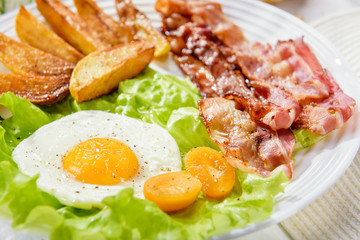Egg with bacon. Fried bacon. Fried bacon with French fries and a delicate egg, close-up.