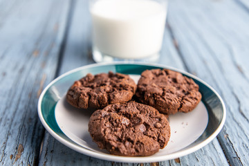 A cup of milk and a plate of chocolate cookies on blue wooden floor