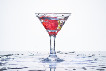 Splash in a glass. Frozen explosion of freshness from water, in a cocktail glass with strawberries. White background.