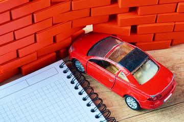 Car insurance concept. Red car crashed in a brick wall