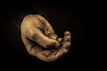 Helping hands concept, Man's hands palms up holding money coins, need care and support, reaching out, aged photo amber
