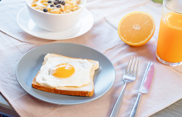 Toast with fried egg, orange juice and cornflakes with milk and berries. Healthy breakfast.