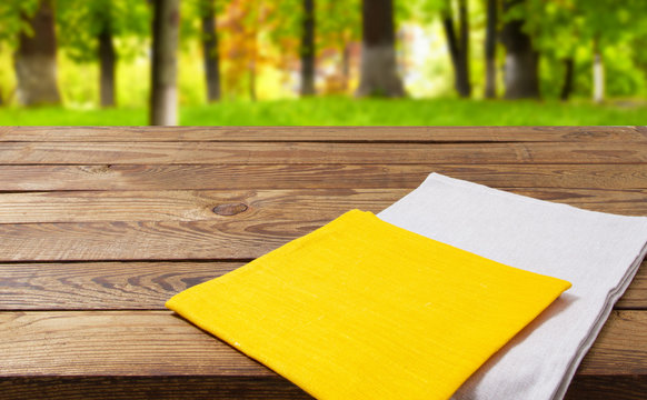 white and yellow napkin on empty wooden table on blurred park baclground,copy space,empty