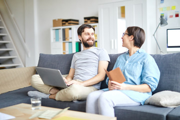 Cheerful young couple discussing where to go for vacations before reserving tickets online