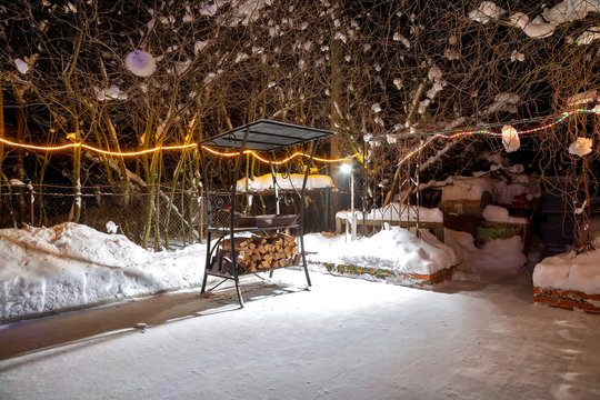 BBQ near the home in the winter. Night, garlands are burning, it is snowing. Empty playground. They lay harvested firewood under the grill