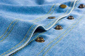 Blue washed faded jeans texture with seams, clasps, buttons and rivets