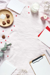 Valentines day, wedding stationery mockup scene. Candle, paper hearts confetti, chocolate, eucalyptus branch and blank greeting cards. Pink linen background. Love concept. Vertical flat lay, top view.