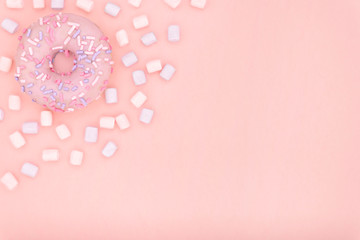 Donut and marshmallow sweet dessert with colorful sprinkles flat lay on pastel coral paper background. Doughnut minimal concept. Copy space