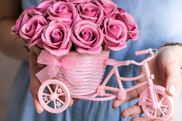 Festive floral decor: a small decorative basket in the shape of a fork with pink flower buds in the hands of a girl.