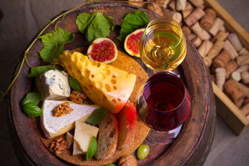 Glasses of red and white wine with cheese, bread and nuts on old cask in wine cellar. horizontal