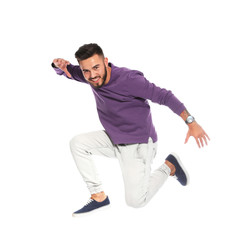 Handsome young man jumping on white background