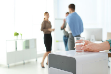 Office employee with glass near water cooler at workplace, closeup. Space for text