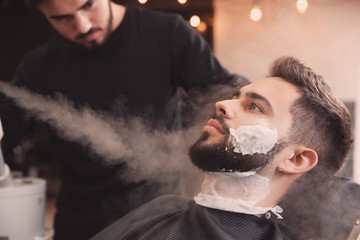 Hairdresser working with client at barbershop. Professional shaving service