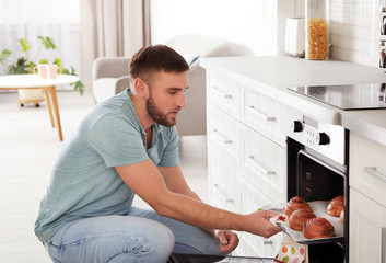 Young man taking out tray of baked buns from oven in kitchen