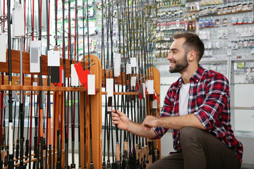 Man choosing fishing rod in sports shop. Space for text