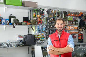 Door stickers Hunting Salesman standing near showcase with fishing equipment in sports shop. Space for text