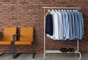 Wardrobe rack with men's clothes and shoes near brick wall