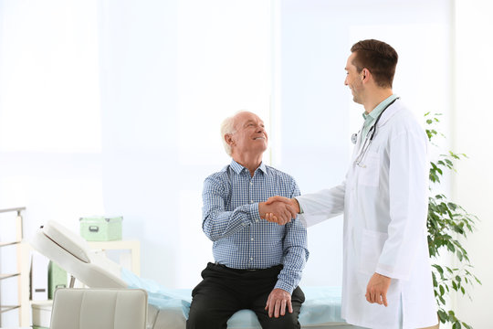Doctor and elderly patient shaking hands in hospital. Space for text