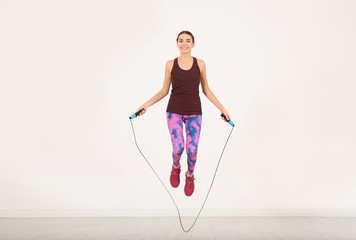 Full length portrait of young sportive woman training with jump rope in light room