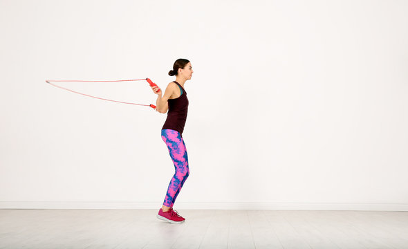 Young sportive woman training with jump rope in light room