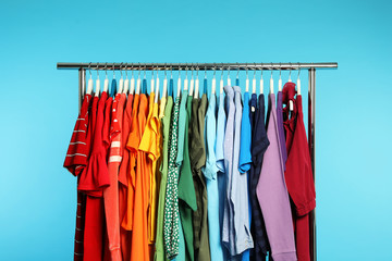 Wardrobe rack with different bright clothes on color background