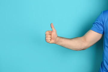 Young man showing thumb sign on color background Wall mural