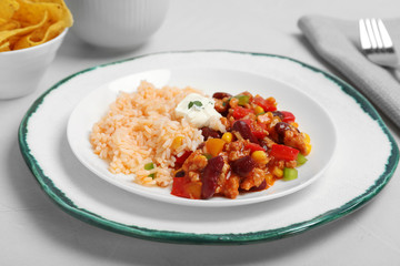 Chili con carne served with rice and sauce on table