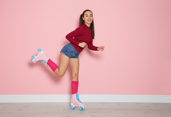 Young woman with roller skates near color wall
