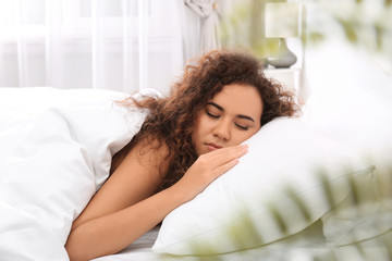 Young African-American woman sleeping on soft pillow at home. Bedtime