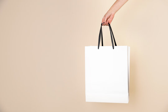 Woman holding paper shopping bag on color background. Mock up for design