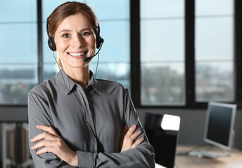 Female technical support operator with headset in office. Space for text